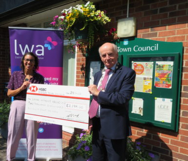 Tom presenting cheque to Living Without Abuse